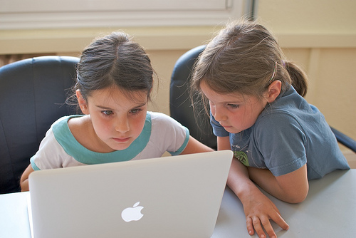 photo: two girls working together on a Mac