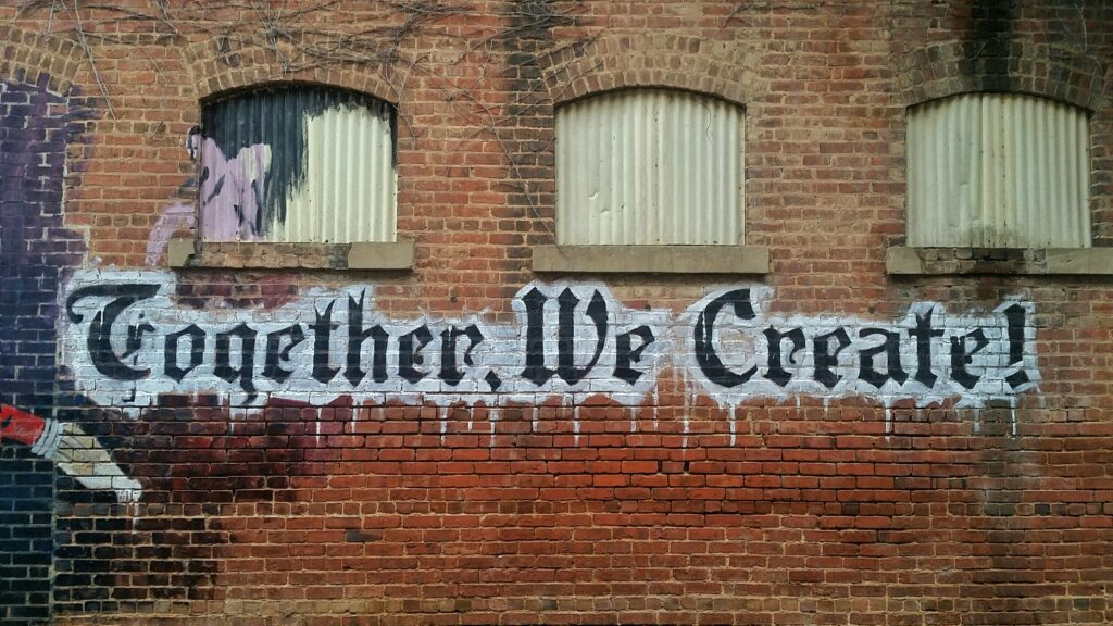 """Red brick wall with graffiti letters written to remind us that """"Together We Create"""""""